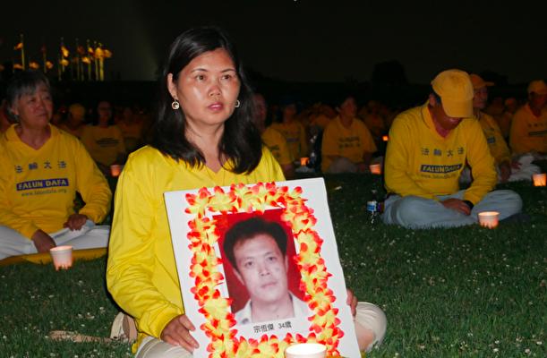 2021年7月16日晚,法輪功學員王福花參加燭光夜悼活動,手持一位被迫害致死的法輪功學員遺照。(李辰/大紀元)