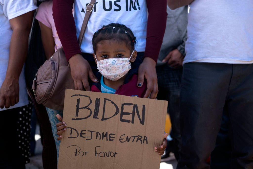 2021年3月2日,在墨西哥蒂華納市的聖伊西德羅口岸,來自洪都拉斯的一位女孩在示威中舉著牌子,要求美國總統拜登讓她入境,要求美國移民政策更加明確。(GUILLERMO ARIAS/AFP via Getty Images)