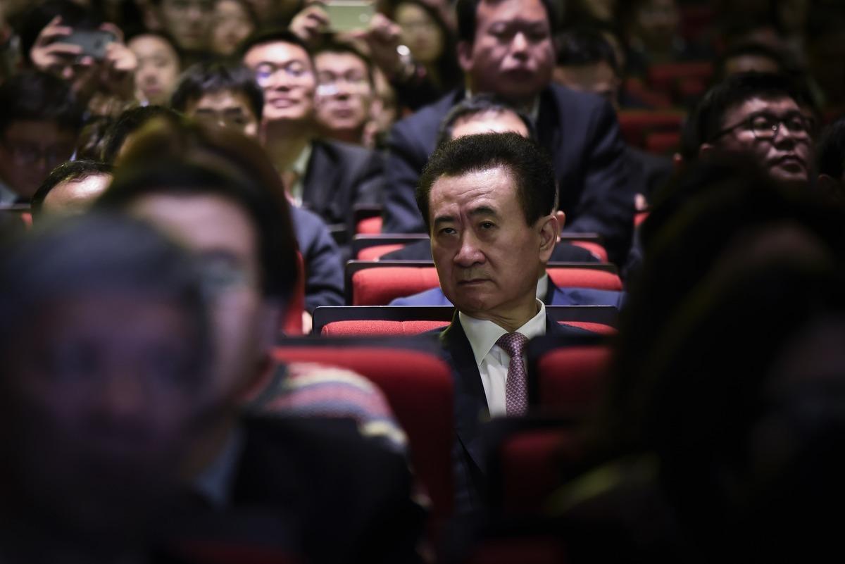 大連萬達集團旗下的萬達體育宣佈將從美股退市。圖為萬達集團董事長王健林(中)。 (AFP)