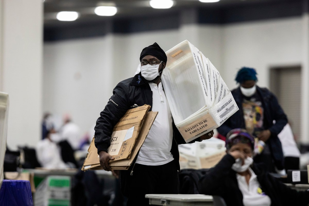 圖為11月4日在底特律TCF會展中心工作人員拿著清空的裝有郵寄選票的箱子。(Elaine Cromie / Getty Image)
