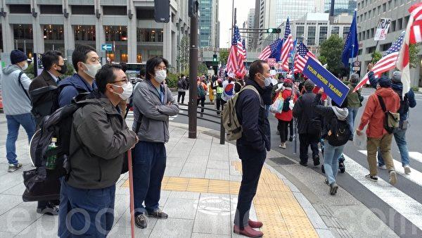 2020年11月29日,民眾們在日本東京發起挺特朗普遊行,不少民眾駐足觀看。(洪寧/大紀元)