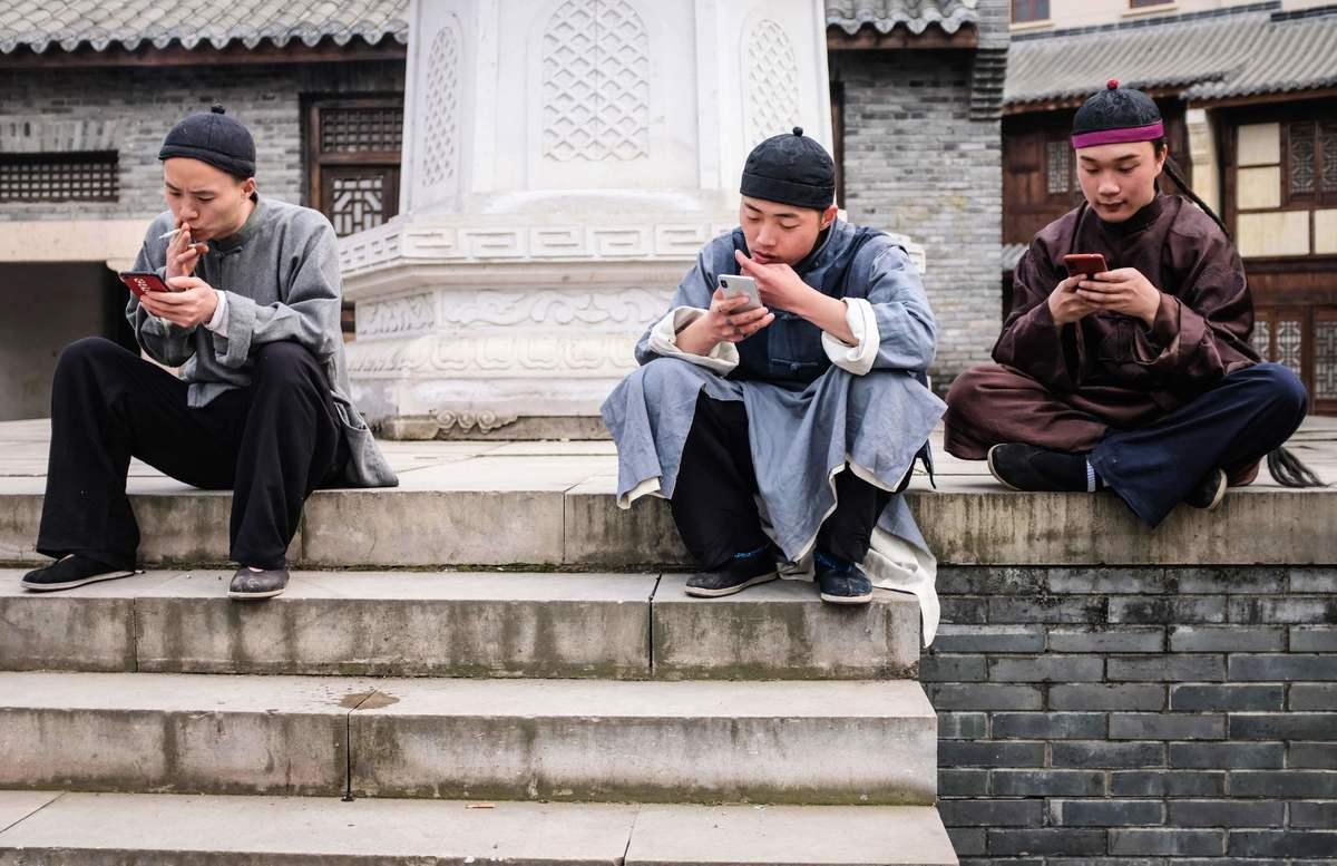 橫店影視城和身處其中的演員正在經歷一場「寒流」,許多群眾演員會在網上開直播,通過獲得粉絲打賞賺錢。圖為橫店的群眾演員在玩手機。(大紀元資料室)