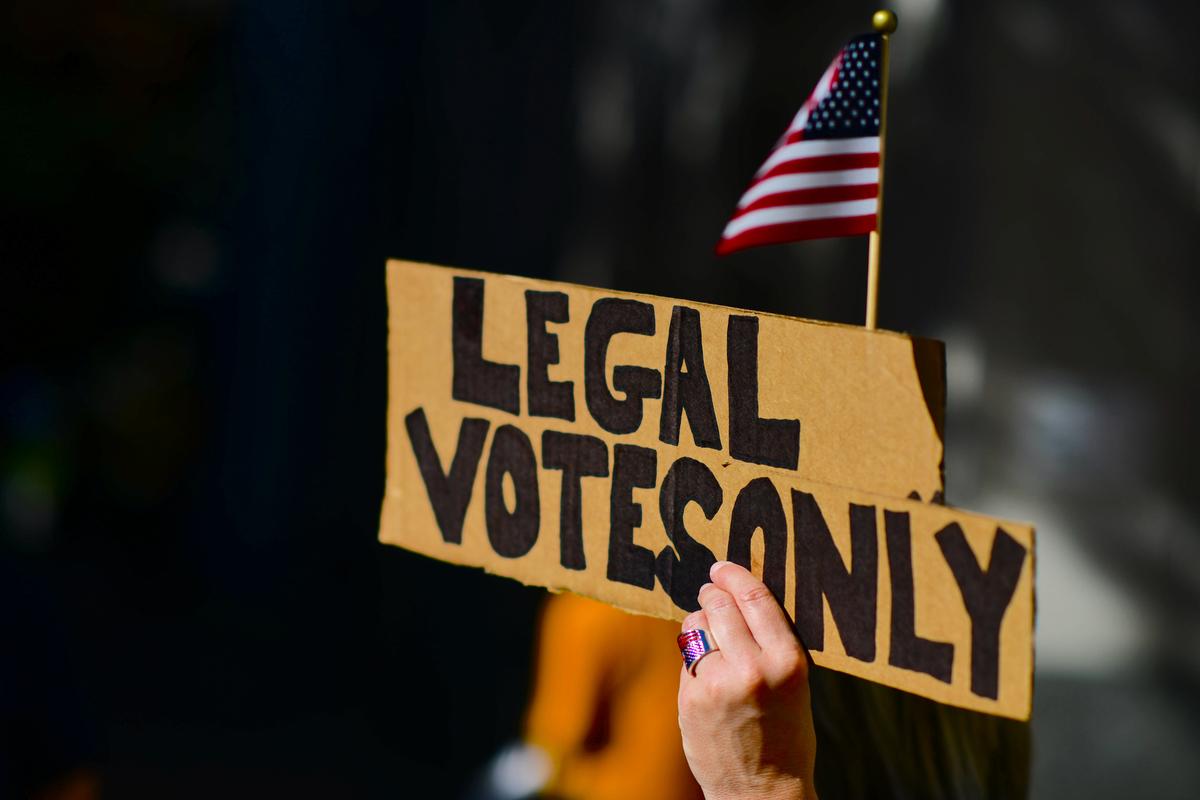 圖為2020年11月10日,特朗普總統的支持者在賓夕凡尼亞州的點票機構外示威,舉著一個寫著「合法投票」的牌子。(Mark Makela/Getty Images)