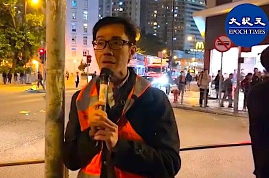 12月6日,周偉雄向記者解釋,在葵青聯校集會有青年因展示「五大訴求 缺一不可」橫額,遭警察帶走(大紀元影片截圖)