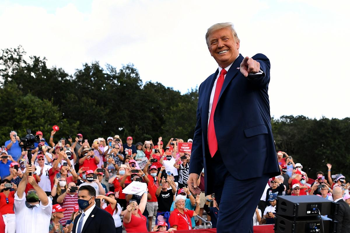 圖為2020年10月23日,美國佛羅里達州群村(The Villages),總統特朗普在「群村馬球俱樂部」舉行競選集會,他到達會場時向支持者致意。(MANDEL NGAN/AFP via Getty Images)