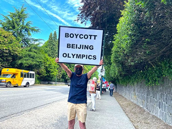 溫哥華居民Ken舉著寫有「BOYCOTT BEIJING OLYMPICS(抵制北京冬奧會)」字樣的標語牌。(梁月/大紀元)