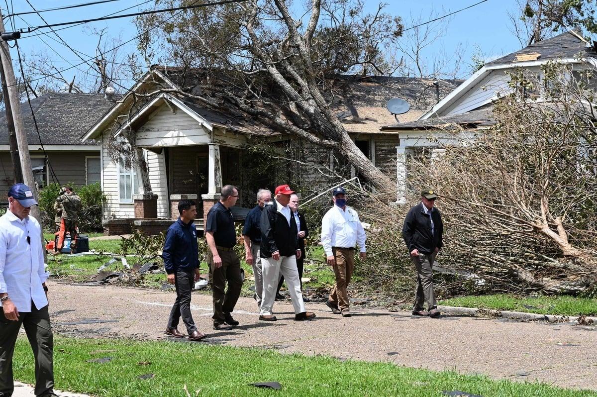 8月29日,美國總統特朗普(紅色帽子)來到路易斯安那州的查理斯湖地區,查看颶風「勞拉」所造成的破壞。(ROBERTO SCHMIDT/AFP via Getty Images)