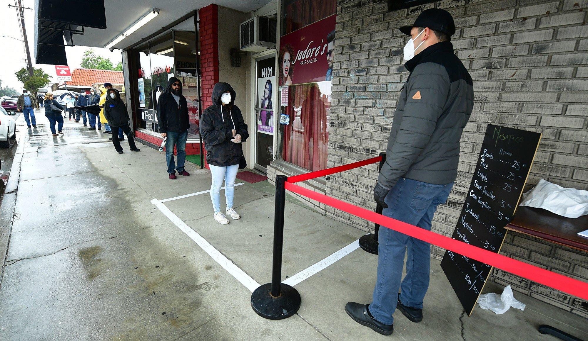 圖為2020年4月9日美國加州民眾排隊等待進入店內消費,均嚴格遵守社交距離規定。(FREDERIC J. BROWN/AFP via Getty Images)