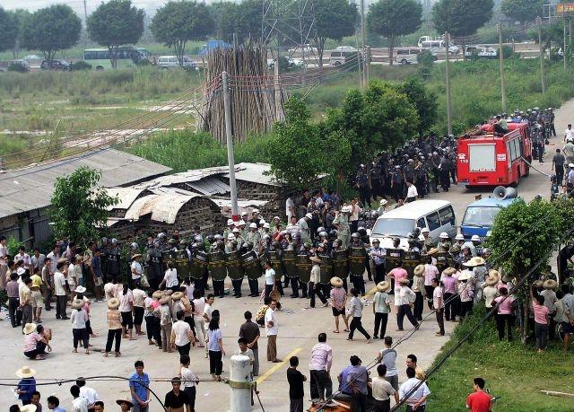 《大紀元》獲得的內蒙古內部文件揭示出,中共已經爛到根,基層政權潰爛不堪。圖為2005年,廣東省番禺太石村村民抗議村官貪腐,番禺政府派出武警彈壓。(大紀元圖片)