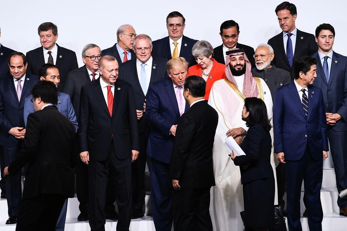 6月28日,特朗普總統與習近平在G20峰會拍大合照前握手。(BRENDAN SMIALOWSKI/AFP/Getty Images)