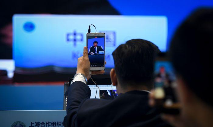 圖為2018年6月10日,中共國家主席習近平在中國青島舉行的上海合作組織(SCO)峰會上發表講話,一名記者在用手機播放現場影片。(WANG ZHAO/AFP/Getty Images)