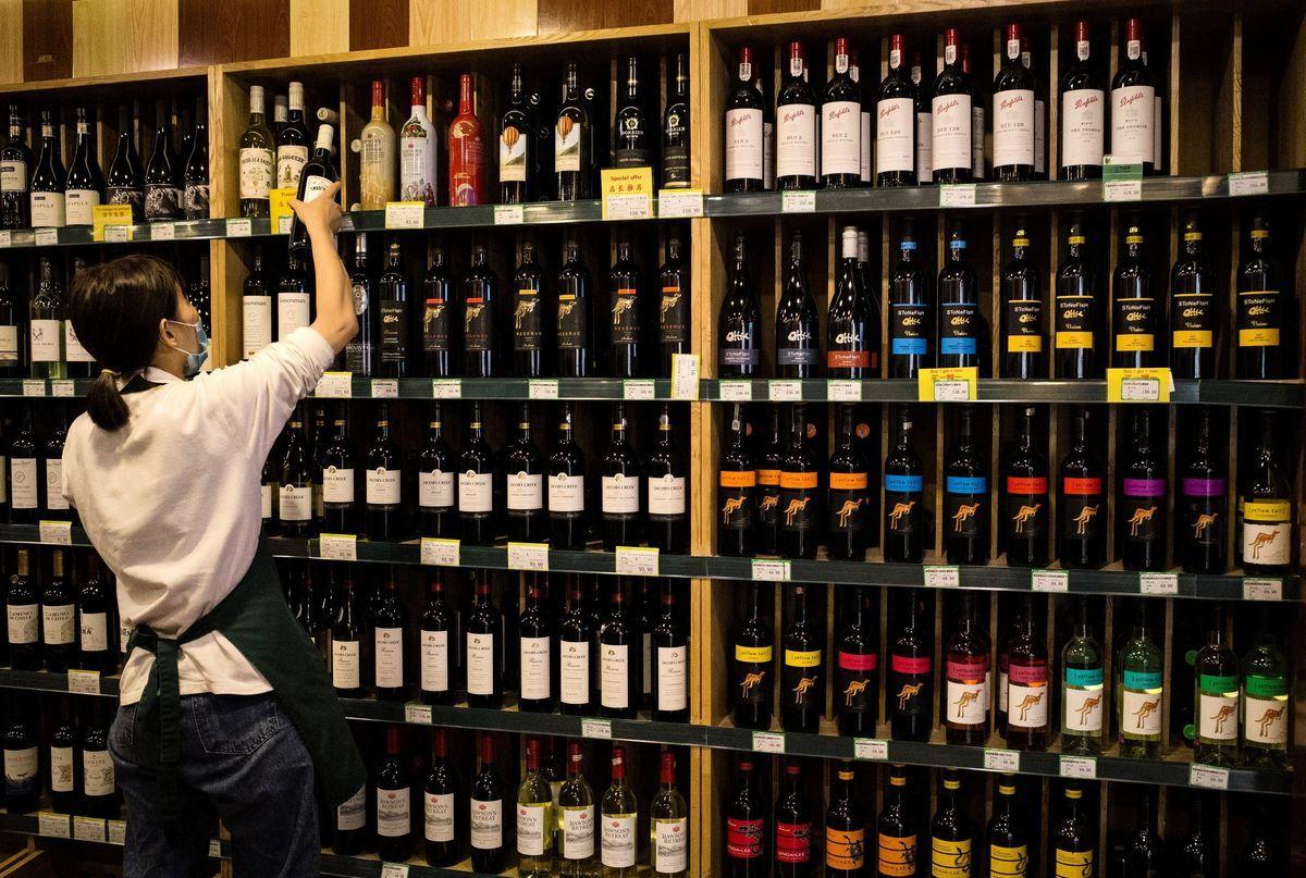 澳洲生產的葡萄酒出口額每年價值30億,而中國又是澳洲葡萄酒需求增長最快的市場。圖為2020年8月18日,北京一家商店中,一名工作人員在澳洲產的紅酒貨架前整理產品。(NOEL CELIS/AFP via Getty Images)