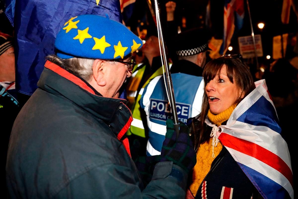 1月29日,英國下議院對脫歐草案修正案進行投票,支持和反對脫歐的陣營在議會外示威,圖為一名支持脫歐的人士(右)和一名戴著歐盟旗幟帽的反對脫歐的人士(左)在對話。(TOLGA AKMEN / AFP / Getty Images)