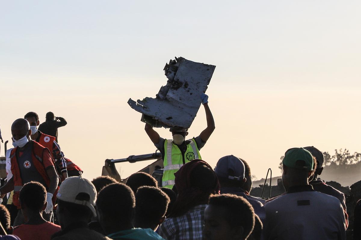 埃塞俄比亞航空(Ethiopian Airlines)一架波音737MAX型班機昨天(3月10日)起飛後不久墜毀,機上157人全數罹難。圖為一名現場人員找到一塊失事客機的碎片。(Michael TEWELDE / AFP)