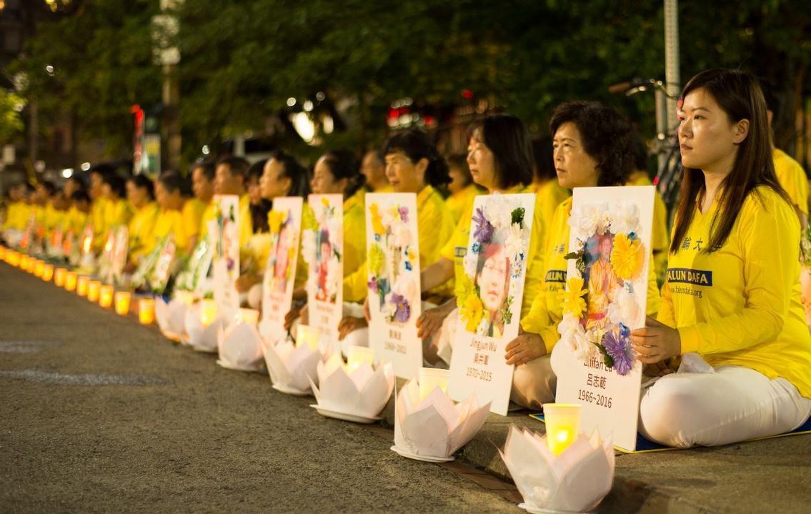 法輪功修煉者於2019年7月13日在中國駐多倫多領事館前舉行燭光守夜活動,並持有在中國遭受迫害殺害的法輪功學員的照片。(大紀元)