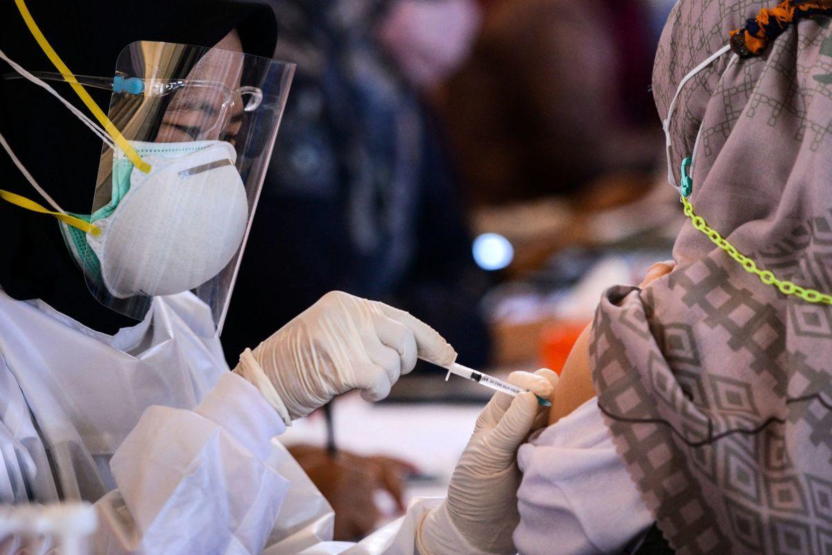 印尼當局表示,超過350名醫療人員儘管接種了中國科興(Sinovac)疫苗,但還是感染了Covid-19,且有數十人因重症住院。圖為印尼班達亞齊一疫苗接種中心裏,一名衛生工作者正為民眾接種科興疫苗。(CHAIDEER MAHYUDDIN/AFP via Getty Images)
