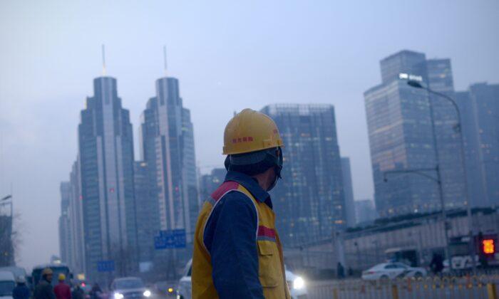 2015年12月28日,一名圖為北京工人下班後沿街行走。(Wang Zhao/AFP via Getty Images)