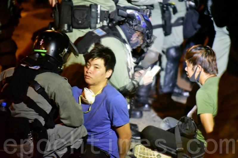 2019年11月19日,當救護員離開香港理工大學時,警察拘捕想離開的人。圖示被捕人數眾多。(余天祐/大紀元)