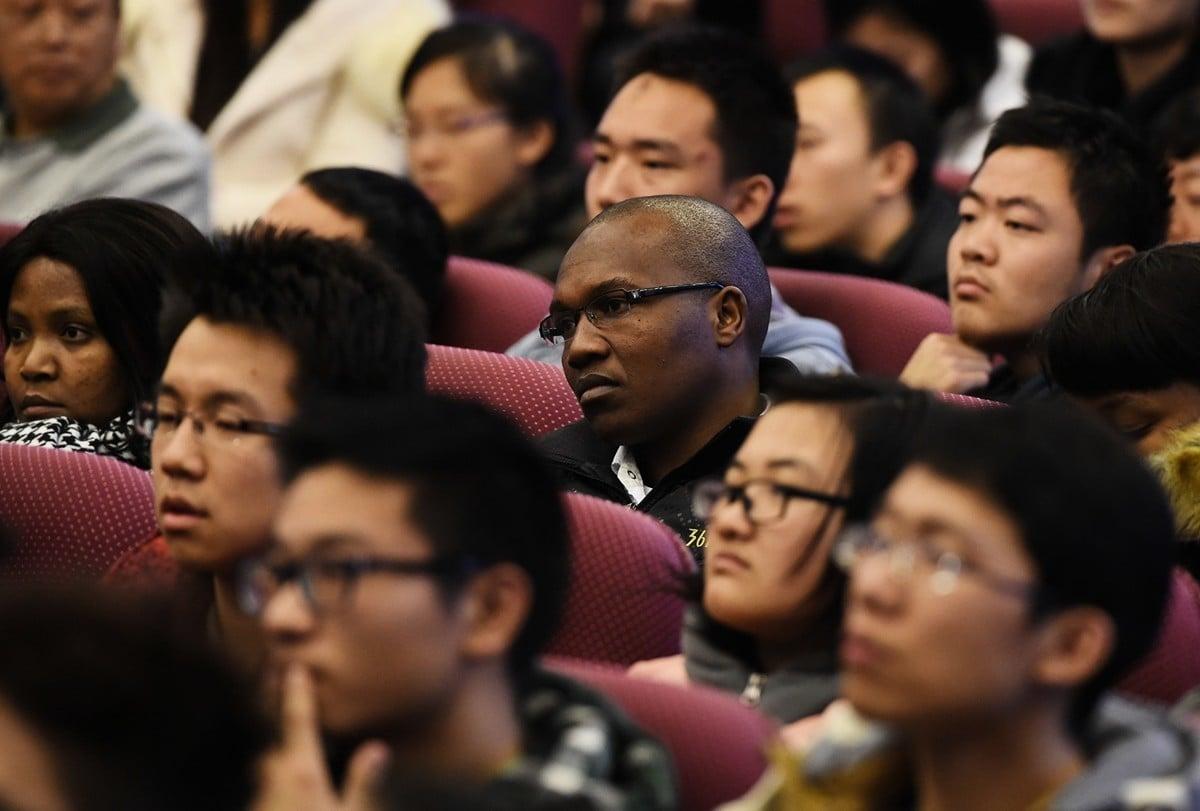 近日,山東大學「學伴」項目醜聞受到輿論廣泛關注。圖為2014年12月5日,南非留學生與中國大學生在北京清華大學聽取訪華的時任南非總統祖馬演講。(AFP/Getty Images)