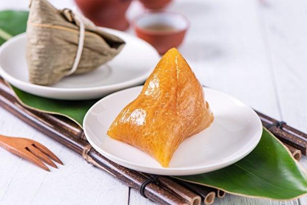 「角黍包金」的黃金色鹼粽,表現端午時節「陰陽尚相包裹未分散之時象」。(shutterstock)
