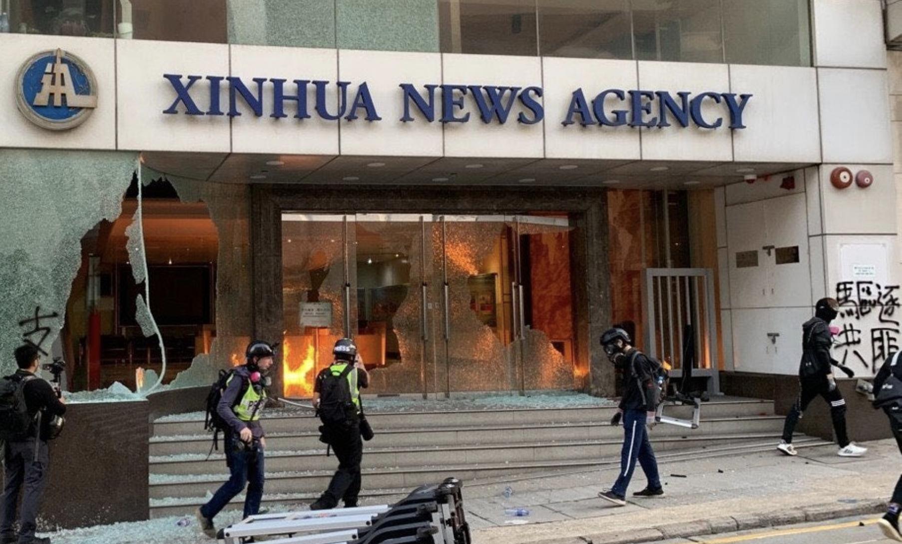 圖為2019年11月2日,香港示威者「快閃」火燒新華社。(Getty Images)