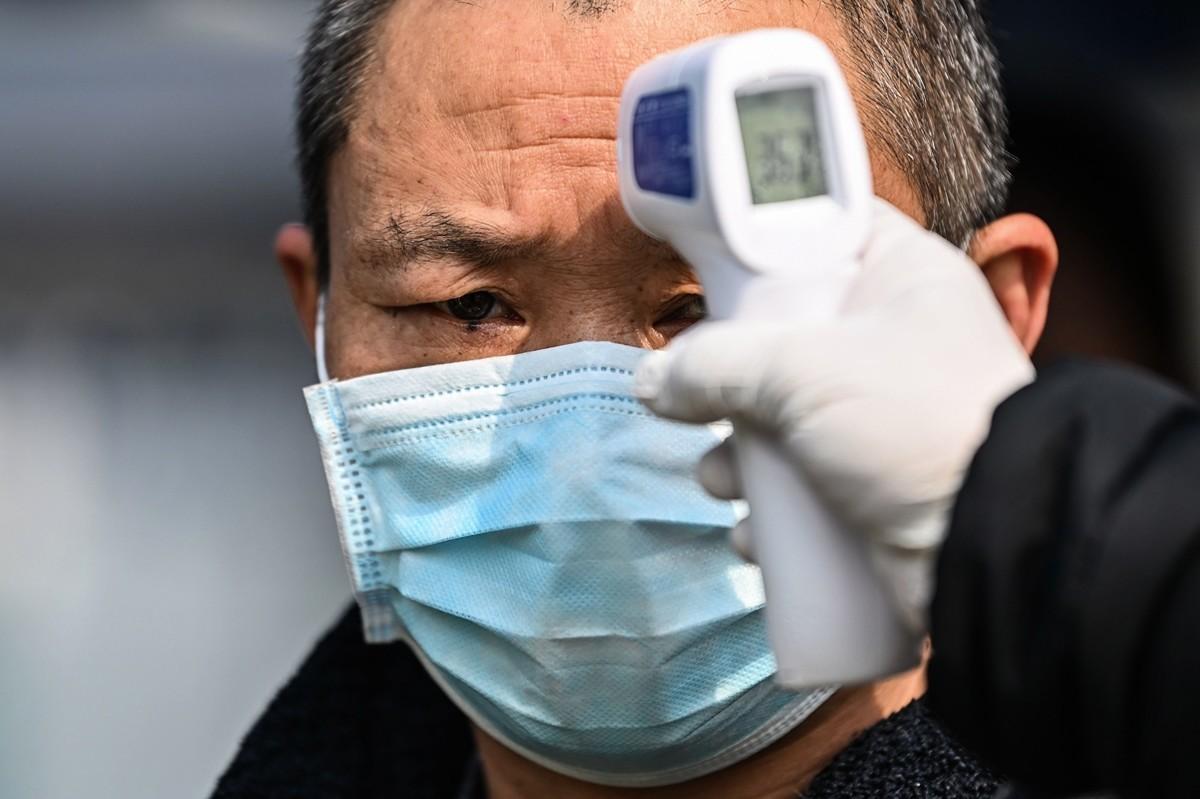 2020年4月4日,一名男子離開湖北武漢市的漢口火車站時進行了體溫檢查。(HECTOR RETAMAL/AFP via Getty Images)