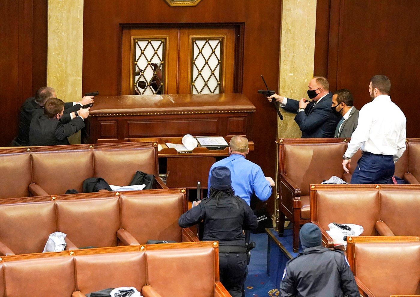 2021年1月6日,美國國會舉行聯席會議認證總統。反對大選舞弊和支持特朗普的民眾議會大樓外聚集。圖為國會山警察舉著槍對著議會大廳的一扇門,門外是衝進大樓的抗議者。(Drew Angerer/Getty Images)