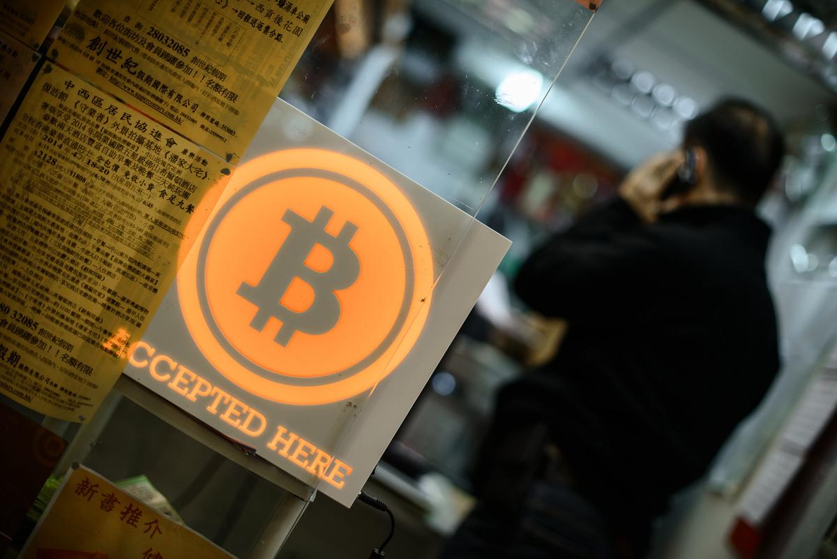 中國很少在金融領域作為早期的嘗試者,但為甚麼在數碼貨幣的推出中,先聲奪人?可能有七個原因。圖為香港一個加密數碼貨幣的招牌。(PHILIPPE LOPEZ/AFP via Getty Images)