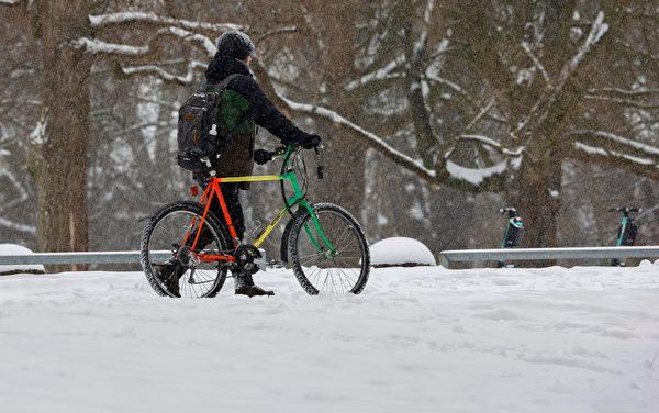 2021年2月8日,德國漢諾威(Hanover),一位市民推著單車在雪中行走。(MORRIS MAC MATZEN/AFP via Getty Images)