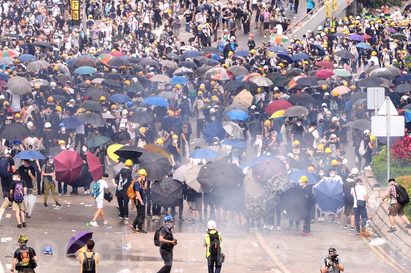 香港「反送中」示威衝突升級,民眾帶頭盔雨傘等保護用品,但警方12日下午在立法會旁,對示威者施放至少150枚催淚煤氣、20枚布袋彈和多次射擊橡膠彈,造成多人受傷。(宋碧龍/大紀元)