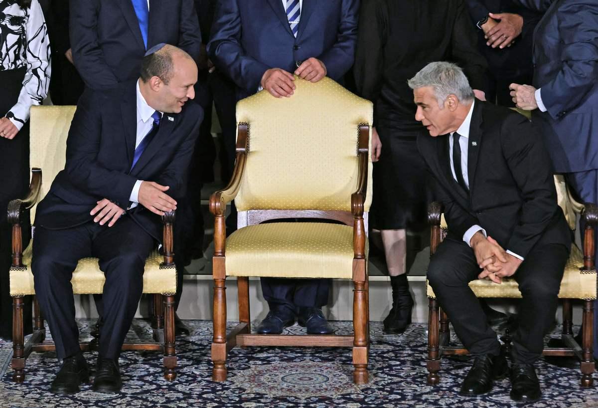2021年6月14日,以色列新總理納夫塔利‧貝內特(Naftali Bennett)(左)和候補總理兼外交部長亞伊爾‧拉皮德(Yair Lapid)(右)在新聯合政府與即將卸任的總統魯文‧里夫林(Reuvin Rivlin)(尚未露面)合照前在總統官邸聊天。(EMMANUEL DUNAND/AFP via Getty Images)
