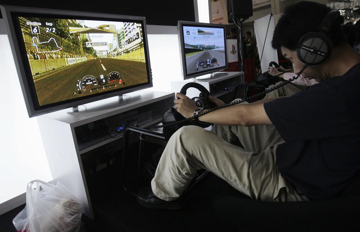 2005年10月3日在北京舉行的第三屆中國國際網際網絡文化博覽會期間,一名遊客在展覽中心玩賽車遊戲。(Getty Images)