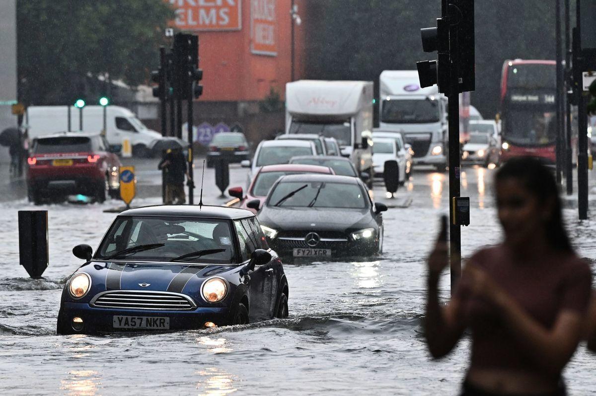 2021年7月25日,倫敦大雨中,許多巴士和汽車發生故障,部份地鐵中斷。圖為汽車正駛過被淹水的路面。(JUSTIN TALLIS/AFP via Getty Images)