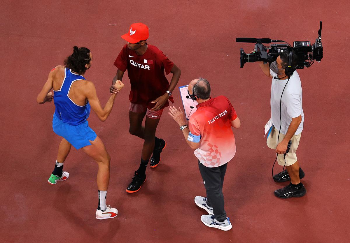 在東京奧運田徑賽場,卡塔爾選手巴爾希姆(左二)和意大利選手坦貝裏(左一)商量後決定,分享男子跳高冠軍。(Richard Heathcote/Getty Images)