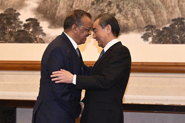 圖為1月28日WHO總幹事譚德塞在北京釣魚台國賓館與中共外長王毅握手。(Getty Images)