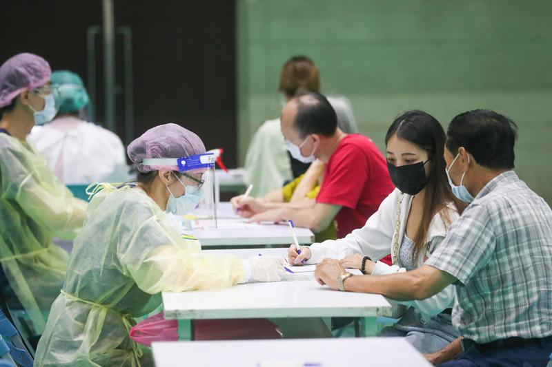 中央流行疫情指揮中心指揮官陳時中3日表示,這兩天以採檢日來看,確診個案確實比較多,但主要是大規模篩檢所致,國內整體疫情趨勢逐漸往下。民眾4日在新北市工商展覽中心填寫資料,準備施打疫苗。(中央社)