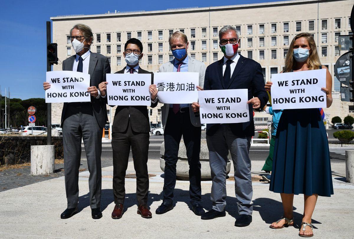 2020年8月25日,意大利羅馬外交部前,羅冠聰與意大利前外交部長朱利奧・特爾吉(Giulio Terzi,左)、眾議員費德里科・莫里科內(Federico Mollicone,右二)、參議員盧西奧・馬蘭(Lucio Malan,中)和勞拉・哈特(Laura Hart,右)舉著標語牌。(TIZIANA FABI/AFP via Getty Images)