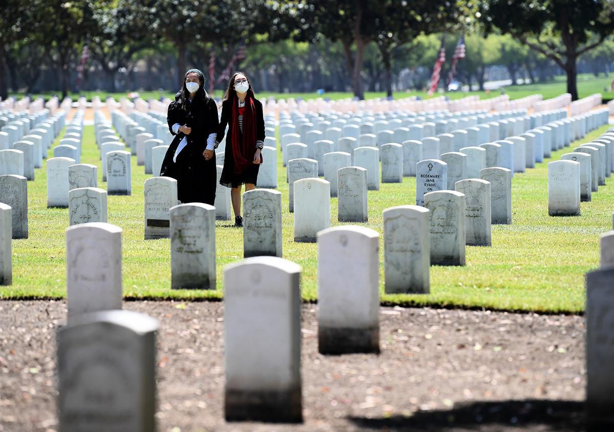 一項新調查顯示,超過七成的美國人對中共持負面看法,為史上最低的評價。近八成的美國人也認為,中共疫情處理不當造成全球大流行。圖為加州洛杉磯國家公墓,戴著口罩的人們在追悼他們的親人。(Harry How / Getty Images)