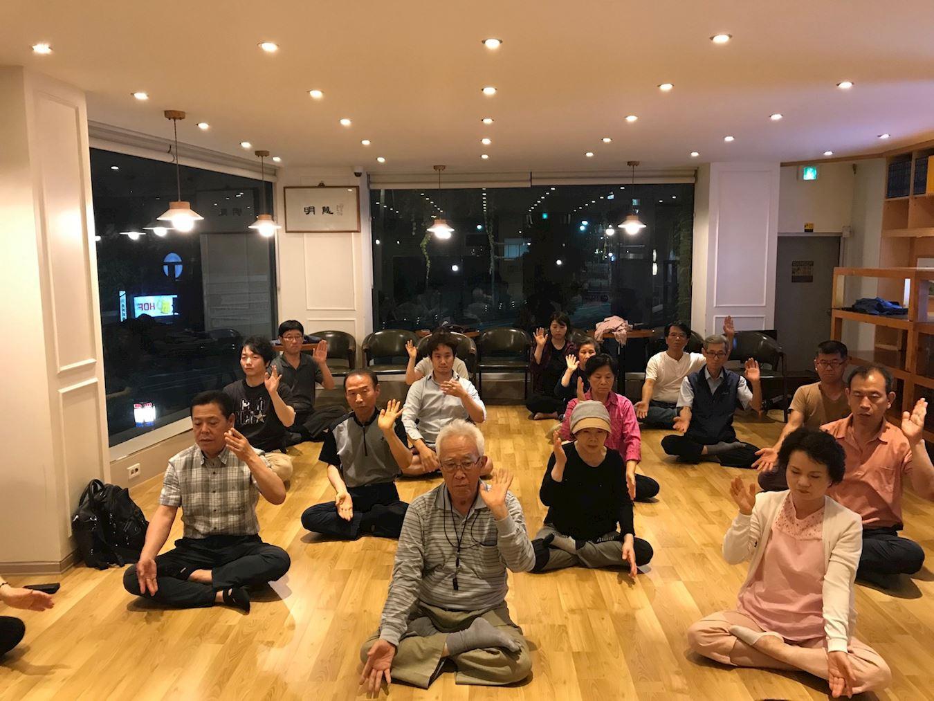 2019年7月,在南韓首爾舉辦的「法輪功九天學習班」上,新入門的學員學煉法輪功功法。(明慧網)