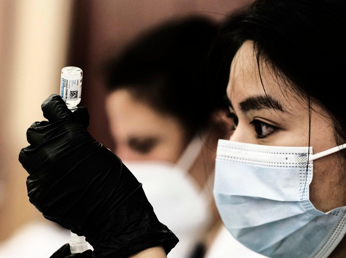 2021年4月12日,在密歇根州底特律Western International High School一個彈出式診所裏,一名藥劑師志願者在準備強生(J&J)中共病毒(武漢肺炎)疫苗。(Matthew Hatcher/Getty Images)