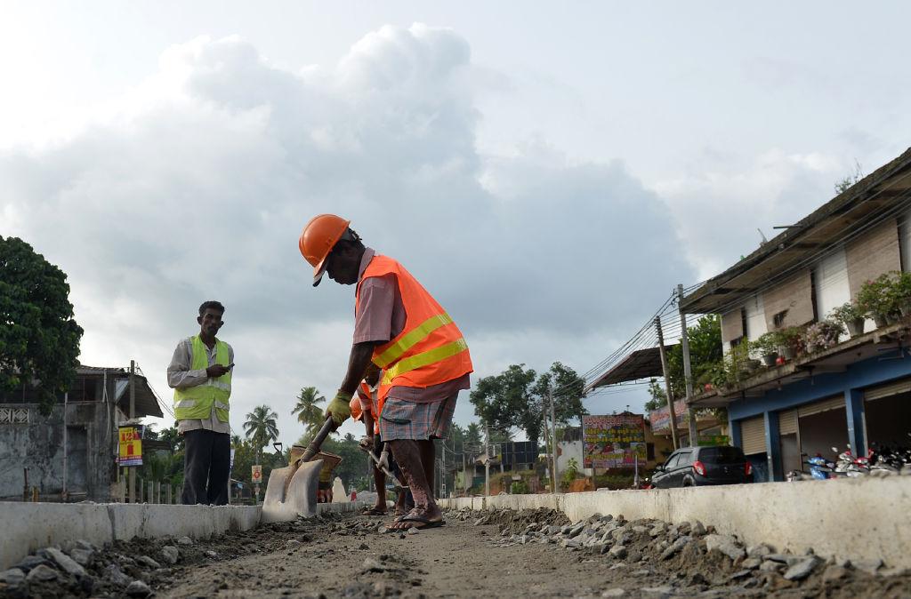 斯里蘭卡因中共的一帶一路計劃揹負鉅額債務,被迫簽署一份長達99年的租約,將具有戰略意義的漢班托塔(Hambantota)港移交給中共。圖為斯里蘭卡工人在修路。(LAKRUWAN WANNIARACHCHI/AFP/Getty Images)