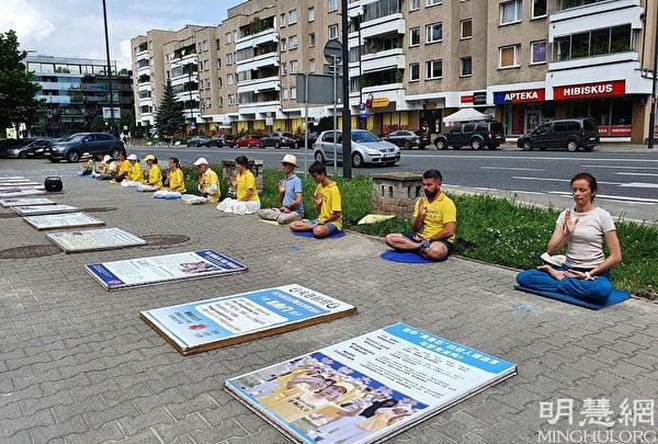 7月18日,波蘭法輪功學員在華沙中使館前靜坐,抗議中共22年的殘酷迫害。(明慧網)