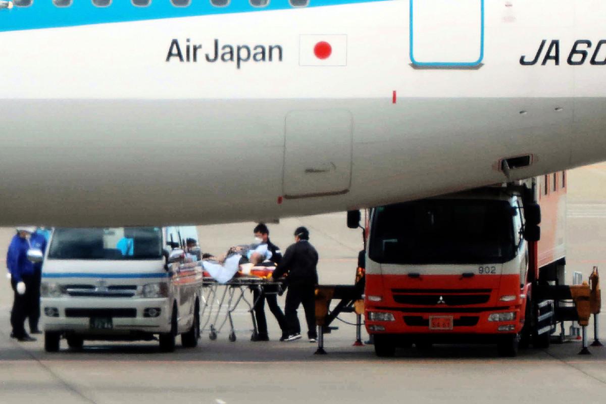 日本向武漢援助了大量醫療物品,一些包裝箱上印有漢詩,引起大陸網民熱議。圖為2020年1月31日,日本政府安排的從中國武漢出發的第三次包機航班抵達東京羽田機場後,被撤離的一名乘客被擔架運送。(Photo by STR / JIJI PRESS / AFP)