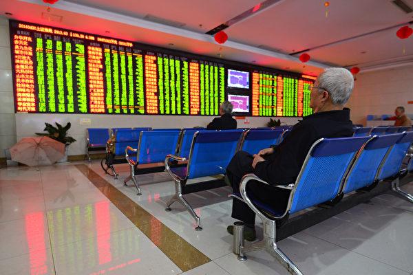 圖為2016年4月20日,投資者坐在安徽省阜陽一家證券公司股市走勢屏幕前。 (STR/AFP/Getty Images)