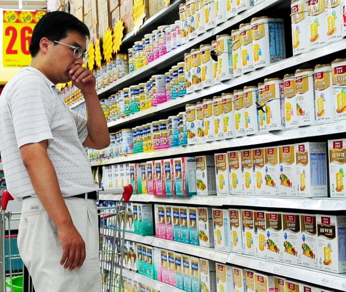 1月14日「中國食品安全風險治理研究成果報告會」上,大陸學者稱要應對食品安全「謠言」,被民眾指事實打臉。圖為北京一位男子在超市猶豫不知該選購何品牌的奶粉。(Franko Lee / AFP)