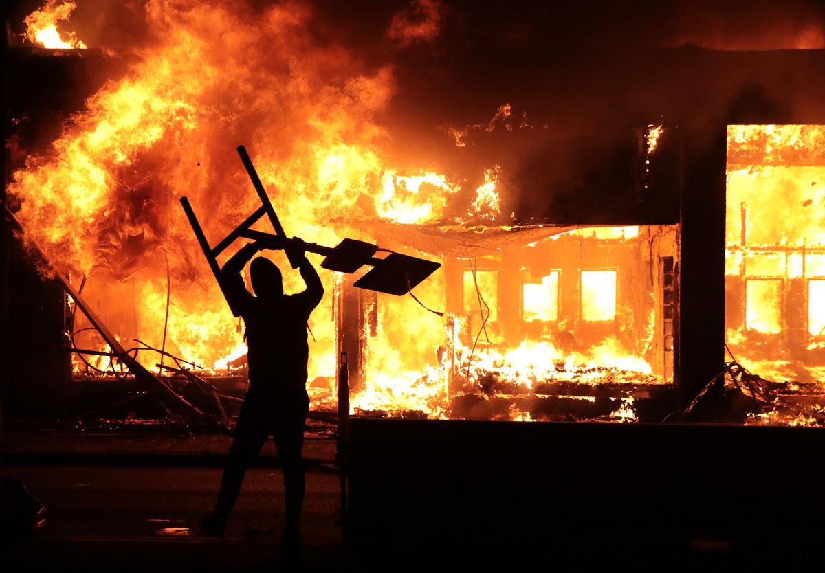 非裔男子喬治·弗洛伊德(George Floyd)之死引發暴動。圖為2020年5月29日示威者點燃一座建築。(Scott Olson/Getty Images)