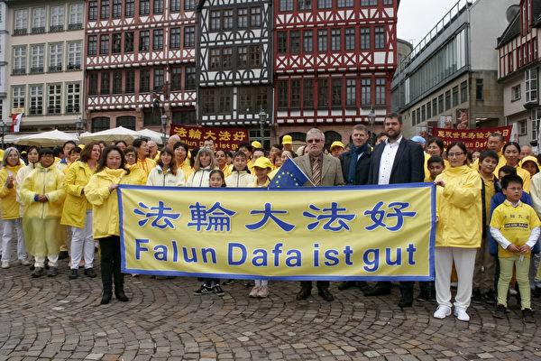2019年5月11日,戛勒先生(前排持歐盟旗幟者)在法蘭克福羅馬人廣場,和德國部份法輪功學員共同慶祝世界法輪大法日。(曹工/大紀元)