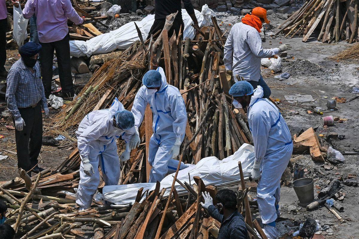 2021年4月27日,攜帶PPE套件(個人防護裝備)的家庭成員和救護人員在新德里的火葬場上運送死於中共病毒(武漢肺炎)患者的遺體。(PRAKASH SINGH/AFP via Getty Images)