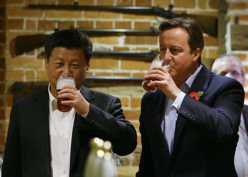 英國和中共曾經的「黃金時代」正在慢慢冷卻。圖為2016年10月22日,時任英國首相卡梅倫和習近平在一家鄉村酒吧品嚐英國艾爾酒。(Kirsty Wigglesworth-WPA Pool/Getty Images)