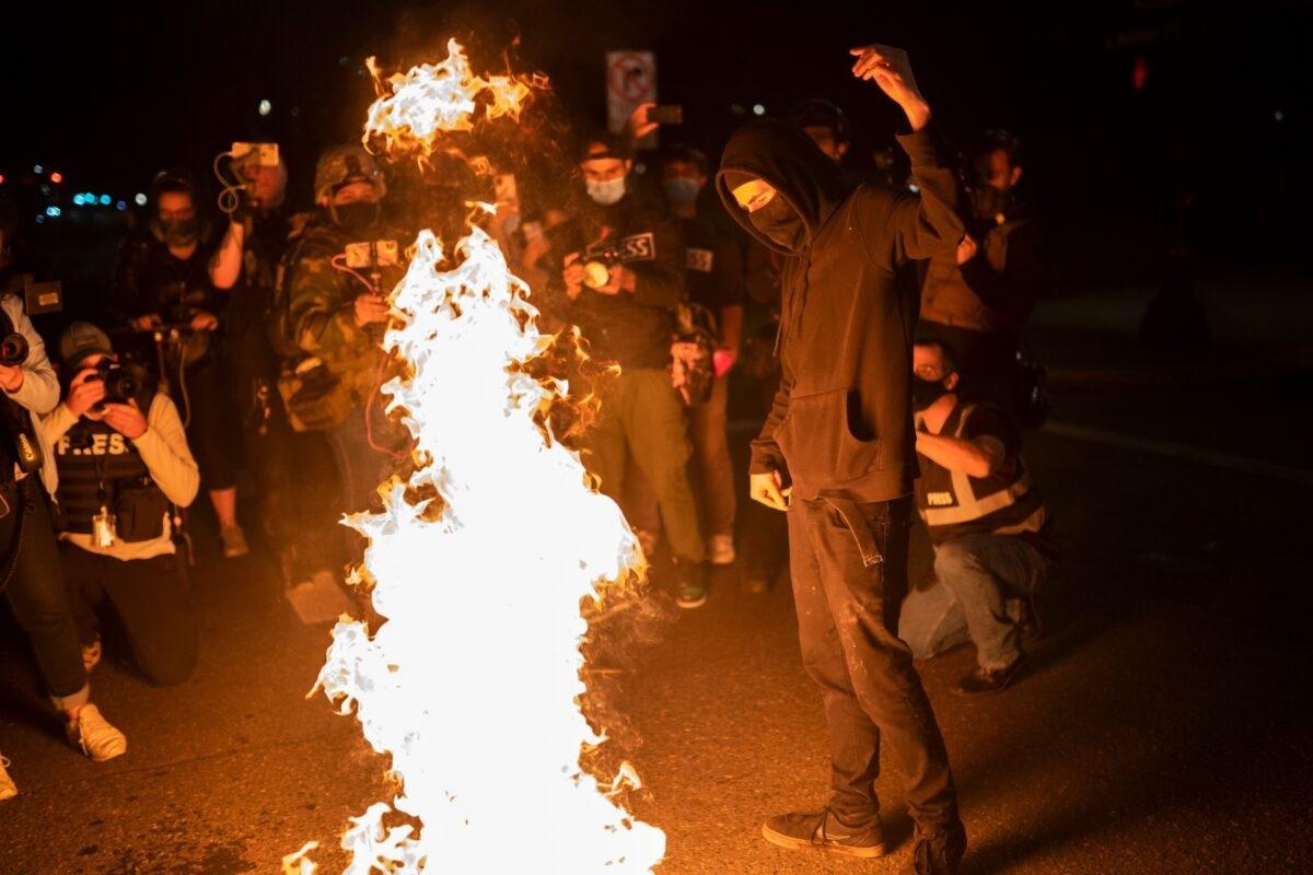 2020年9月26日,抗議人士在俄勒岡州的波特蘭燒燬美國國旗。(Nathan Howard/Getty Images)